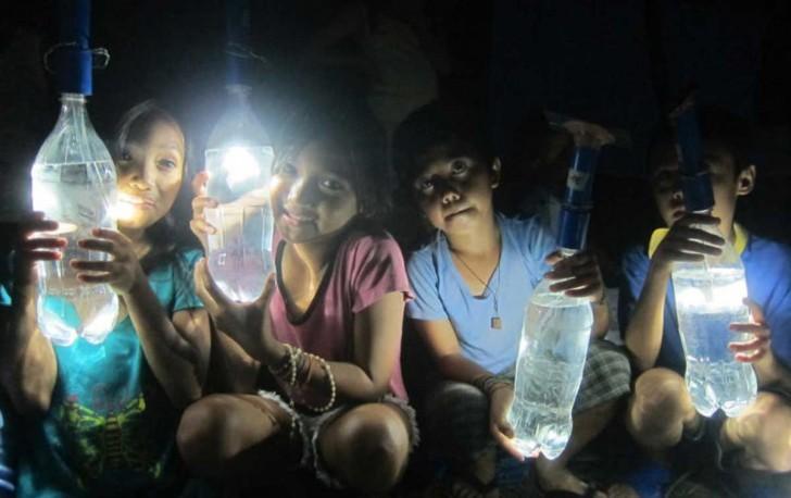Un grupo de niños muestra las lámparas recicladas.