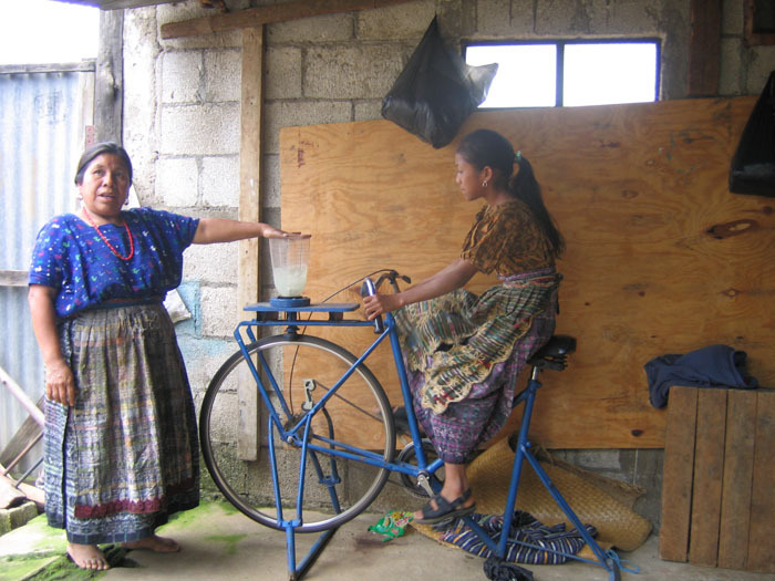 Bi emakume bizikleta-makina batekin zukua egiten.
